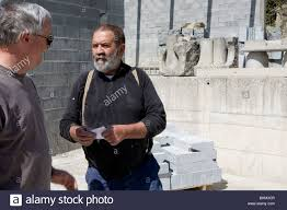 pierre a stonecutter talks with a client who is ordering a