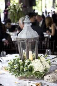Wedding Centerpiece Lantern by Lanterns On Stacked Books W Sprigs Of Flowers Scattered Around