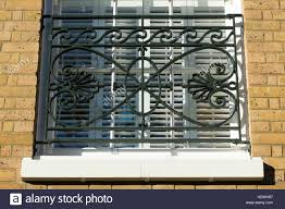 looking up at a modern home window with ornamental security bars