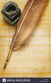 old writing paper old papyrus paper and feather quill with glass ink bottle and copy old papyrus paper and feather quill with glass ink bottle and copy space