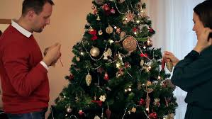 young couple decorating christmas tree together stock footage