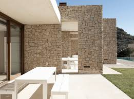 minimalist stone house with open courtyards and simple solid