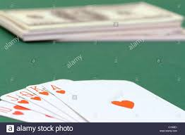 card game table cloth royal flush cards put on green table cloth with pile of dollars in
