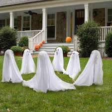 six white ghost ornaments on the green grass of the yard in front