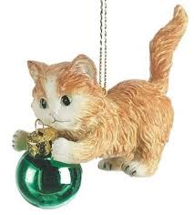 orange tabby kitten with green ornament cat