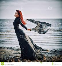 tissu bord de mer belle fille triste de goth avec le tissu dans des mains se tenant