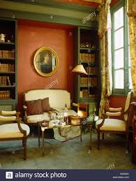 cream upholstered sofa and chairs and gilt coffee table in red