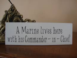 a marine lives here with his commander in chief wood sign