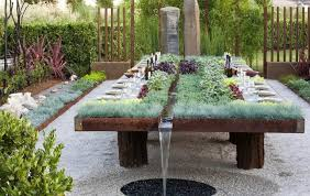 wide planting table with green grass and purple plants near small