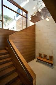 sleek wooden staircase design with modern chandelier above it