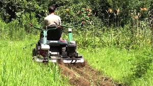 2 tiller shark tow behind by a garden lawn tractor for tilling