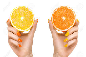 stylish woman hands with orange and yellow colored nails holding