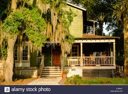 an historic house in low country with rocking chairs on porch with an historic house in low country with rocking chairs on porch with spanish moss hanging from trees in the yard st mary s ga