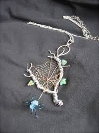 this is a spiderweb pendant i made from twisted wire of different