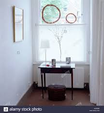 upstairs landing with table ornaments and window stock photo