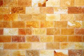 hues of orange architectural background with a wall of colourful stone in hues of