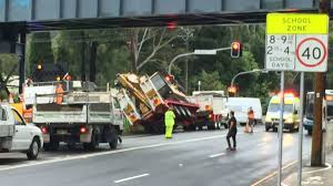 traffic heavy after excavator slips off truck at bulli illawarra
