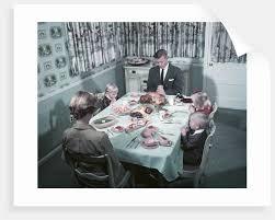 1950s family of 5 saying grace before thanksgiving turkey dinner