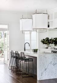 marble waterfall kitchen counter and big fabric pendants earthy