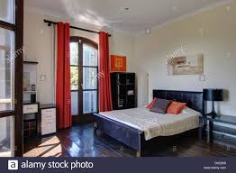 red curtains on french windows in spanish bedroom with black