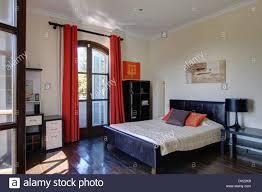 polished dark wood floor in spanish bedroom with beamed ceiling