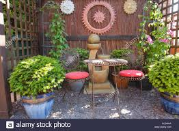 The Urban Garden Arbor In An Urban Garden With Table And Chairs Potted Plants And
