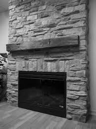 mantel stone and rustic iron shelf on natural wall panel fireplace