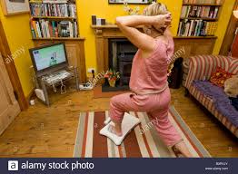 middle aged woman doing her yoga exercises on a nintendo wii fit