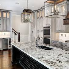 black kitchen island with white and gray granite countertops