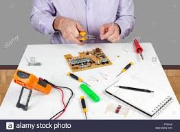 electronic test engineer using long nose pliers to form a circuit