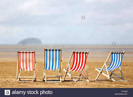 Chairs On A Beach A Row Of Striped Empty Deck Chairs Waiting For Customers On A Warm