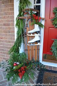 front porch decorated for with three wreaths on door and