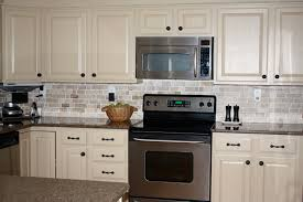love the cream color painted kitchen cabinets with dark hardware