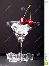 martini black cherry berries in a martini glass on black background stock photo