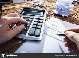 sur le bureau une personne calcul facture avec calculateur sur bureau bois