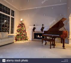 bright christmas tree in living room with burning fireplace and
