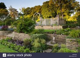 terracing with herbaceous border plants trellis arch u0026 bird bath