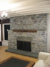 grey stone fireplace with brown wooden mantel shelf and grey tile