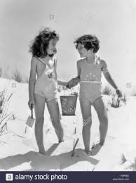1930s two smiling girls sisters friends holding hands and sand