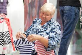 elderly woman clothes elderly woman grandmother choosing baby clothes in the shop stock