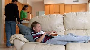mother sitting on couch with two small kids and watching tv set