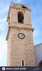 closeup of ancient belfry with clock in spanish mediterranean town