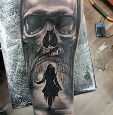 realistic skull and swinging tattoo on forearm by luke sayer