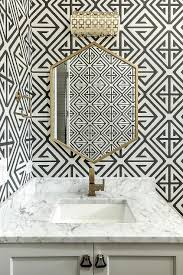 black and white powder room wallpaper with brass sconce