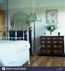 white linen on antique brass bed in townhouse bedroom with art