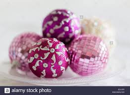 pink and purple christmas decorations on a glass plate stock photo