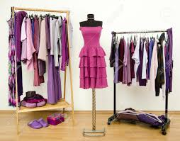 wardrobe with purple clothes arranged on hangers and a dress