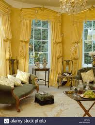 yellow swagged and tailed silk curtains on tall windows in yellow