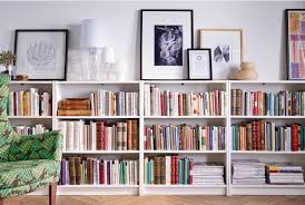 a row of ikea bookcases lines a wall on top is framed art and