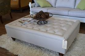 square tufted ottoman coffee table covered by white leather